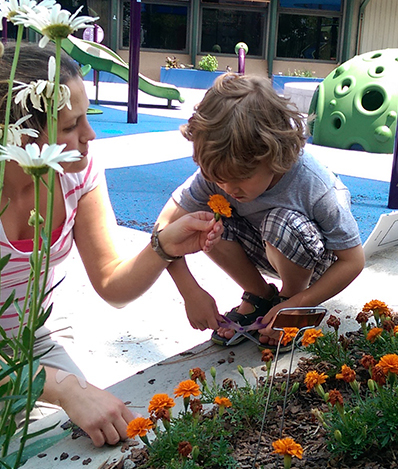 An adult and child are by a playground next to a garden. The child has scissors in their hands and the woman is holding an orange flower to the child's nose to smell.