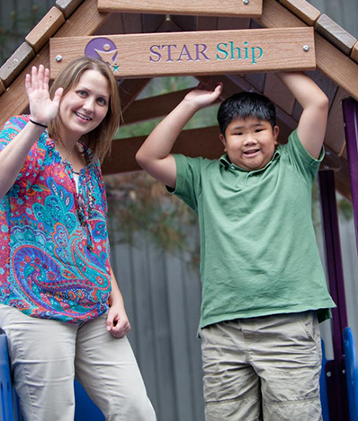 "Child standing under a sign that says ""Star Ship"" smiling at the camera next to a therapist waving at the camera"